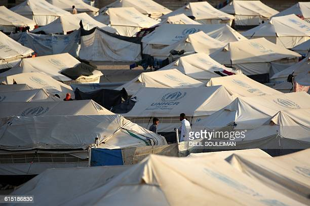 Men stand in between UNHCR tents at a refugee camp housing Iraqi families who fled fighting in the Mosul area on October 17, 2016 in the northeastern...