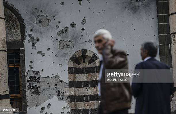 Men stand in front of a bulletriddled wall that was damaged during clashes between Turkish troops and Kurdish militants in the district of Sur in...