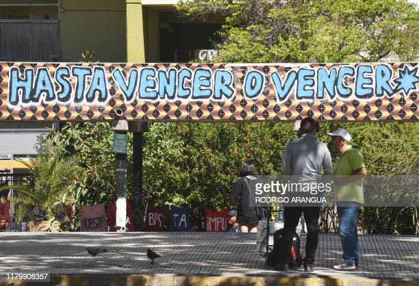 Men stand in front of a graffiti that reads UNTIL VICTORY OR DEATH in Santiago on November 03 2019 Protesters angry about the cost of living and a...