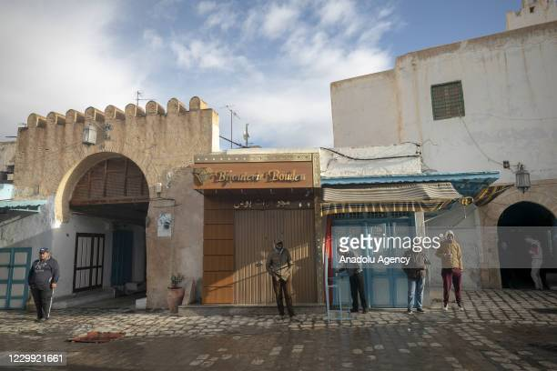 Men stand in front of closed stores as all tradesmen went on a strike on the call of the Tunisian General Workers Union and closed their workplaces...