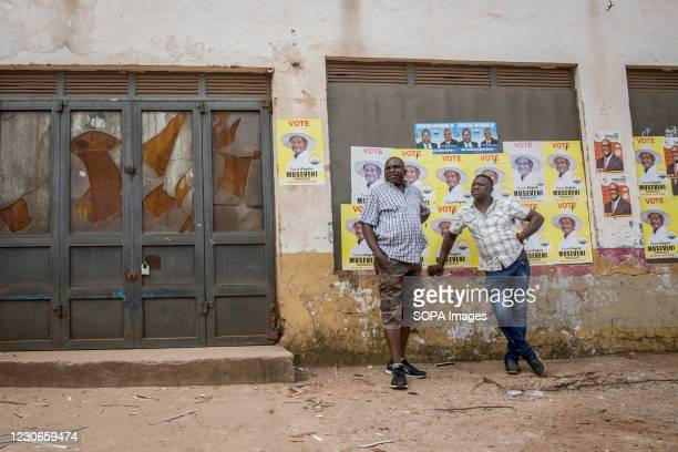 Men stand in front of posters of Yoweri Museveni, Uganda's long-time president. Uganda's elections, on January 14 were the most tense in decades.