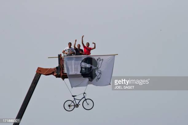 Men stand in the nacelle of a crane with a flag bearing the Moor's Head, the official Corsican symbol, during the 213 km first stage of the 100th...