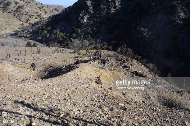 Men stand in two craters from US bombs that laid waste to an Al Qaeda training camp in Milawa one week ago, December 18, 2001 near the Tora Bora area.