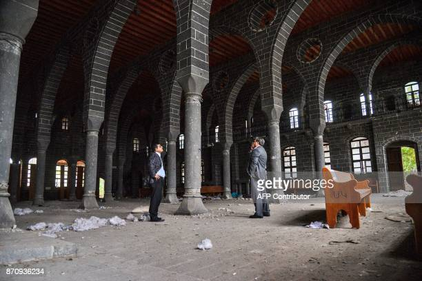 Men stand looking at the damage to the Surp Giragos Armenian church in the historical Sur district of the Kurdishmajority city of Diyarbakir...