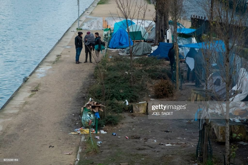 Men stand near tents at a makeshift migrant camp, mainly made up of Afghans, along the Saint-Martin canal in Paris on February 21, 2018. /