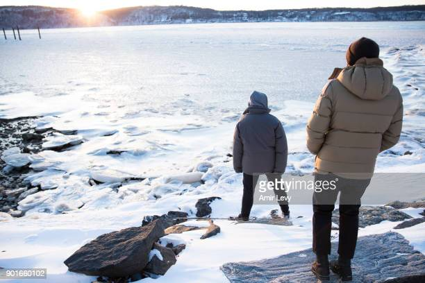Men stand near the frozen Hudson River on January 5 2018 in Dobbs Ferry New YorkExtreme low tempratures and wind are expected throghout the weekend...