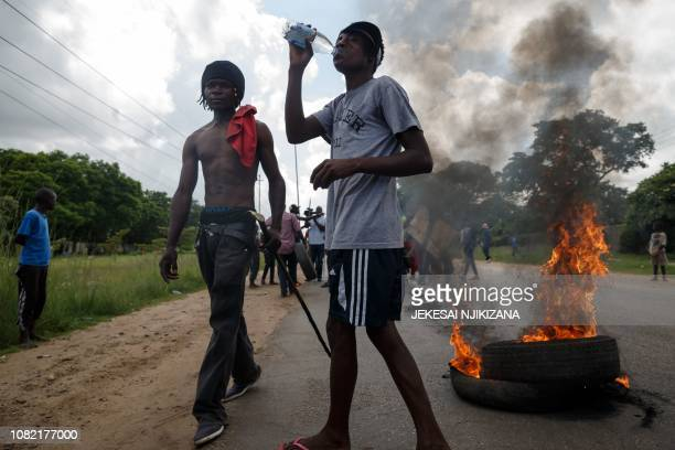 Men stand next to burning tyres as angry protesters barricade the main route to Zimbabwe's capital Harare from Epworth township on January 14 2019...