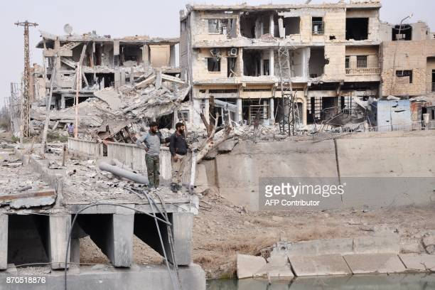 Men stand on a damaged bridge in the eastern Syrian city of Deir Ezzor during a military operation by government forces against Islamic State group...