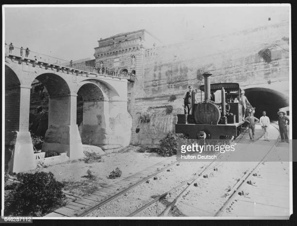 Men stand on and next to a steam locomotive at a railway station next to a viaduct in Malta