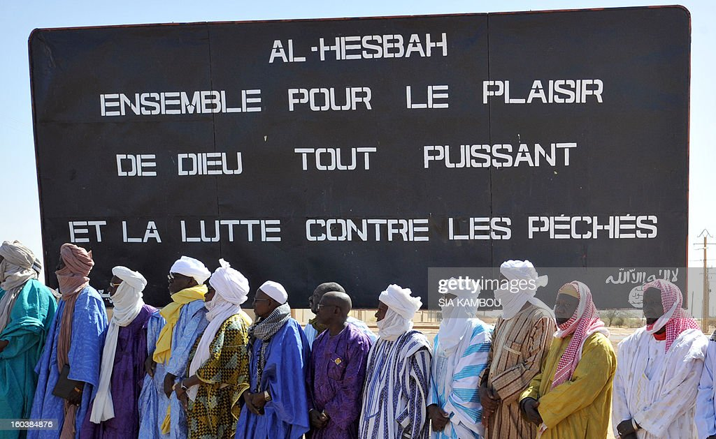 Men stand on January 30, 2013 in front of a billboard left by the Movement for Oneness and Jihad in West Africa (MUJAO), an offshoot of Al Qaeda in the Islamic Maghreb (AQIM), during a ceremony to cleanse the northern city of Gao from traces showing presence of Islamists. Gao was a key Islamist stronghold until it was retaken on January 26 by French and Malian troops in a major boost to the French-led offensive against the Al Qaeda-linked rebels, who have been holding Mali's vast desert north since last April. French troops on January 30 entered Kidal, the last Islamist bastion in Mali's north after a whirlwind Paris-led offensive, as France urged peace talks to douse ethnic tensions targeting Arabs and Tuaregs. Billboard reads: 'Al Hesbah, together for the pleasure of God almighty and the struggle against sins.'