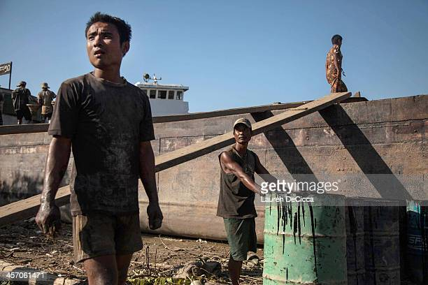 Men stand on the banks of the Irrawaddy River where they work to recycle oil on December 16 2013 in Yangon Myanmar Large cargo ships on the Irrawaddy...