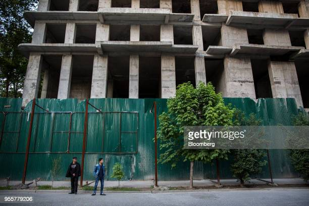 Men stand waiting for a bus known as a 'marshrutka' bus in front of a building under construction in Dushanbe Tajikistan on Saturday April 21 2018...