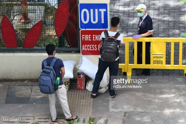 Men stand with their belongings as they talk to a security guard before getting entry into a foreign workers' dormitory, currently under isolation as...