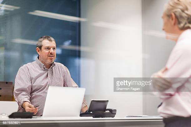 Men standing across and talking in office
