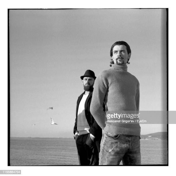 men standing against sea and clear sky - mid adult men stock pictures, royalty-free photos & images
