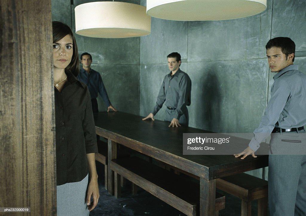 Men standing at table looking at woman standing looking at camera. : Stockfoto
