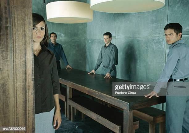 Men standing at table looking at woman standing looking at camera.