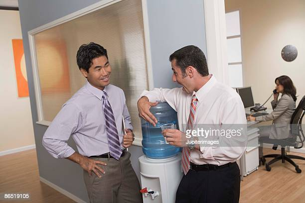 men standing at water cooler in office - water cooler stock pictures, royalty-free photos & images
