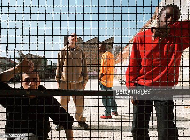 Men standing behind fence in urban playground
