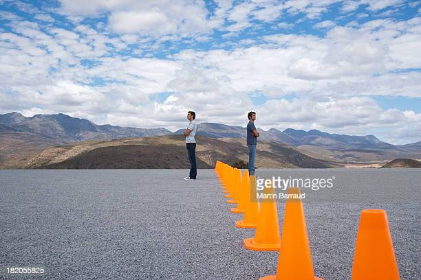 Men standing by rows of safety cones