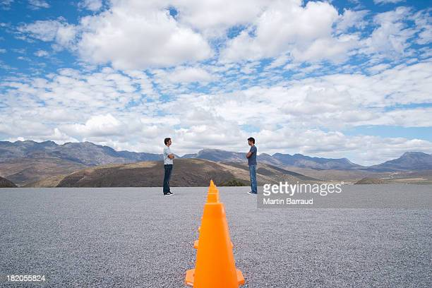 Men standing face to face by rows of safety cones with arms crossed