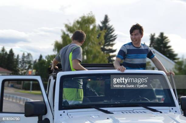 Men Standing In Car Against Sky