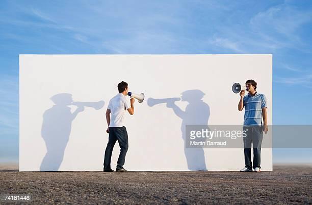 Männer stehen vor einer Wand im Freien mit megaphones