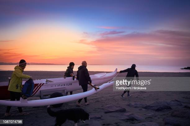 Men standing on beach with canoe at sunrise.