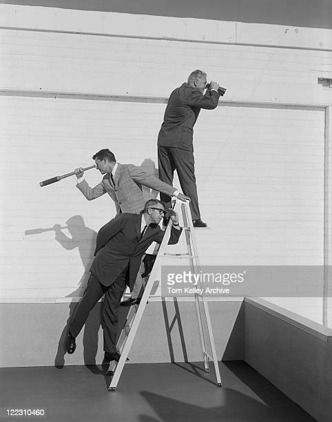 men standing on ladder with binoculars and telescope - archival stock pictures, royalty-free photos & images