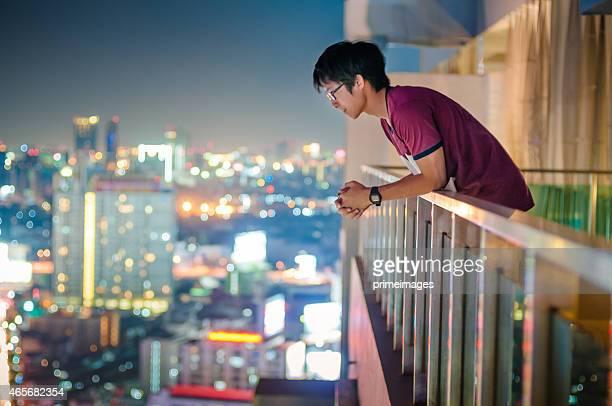男性立つの屋上にあり、超高層ビルの街並みの上に