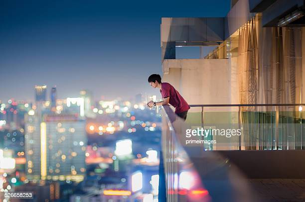 men standing on the rooftop of a skyscraper over  cityscape - balcony stock pictures, royalty-free photos & images