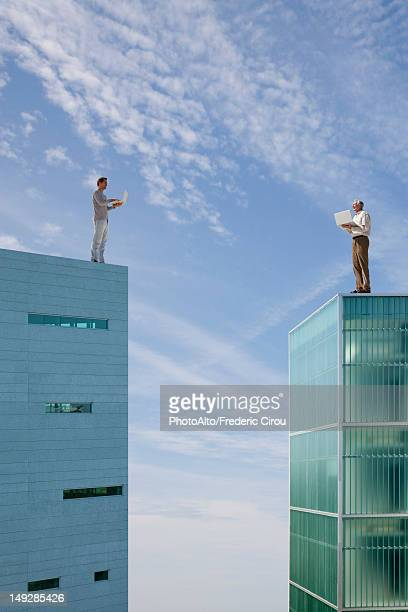 Men standing on top of high rise buildings, using laptop computers
