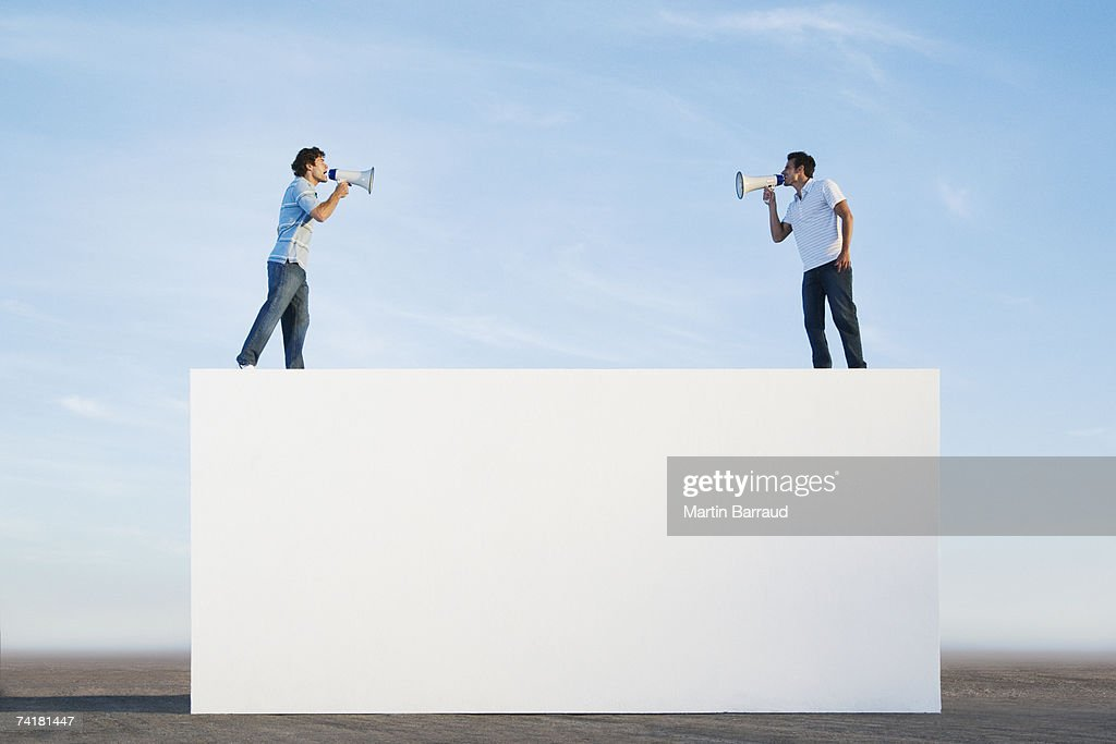 Men standing on wall outdoors with megaphones : Stock Photo