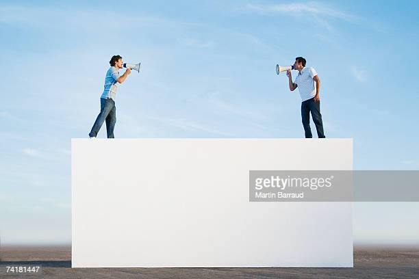men standing on wall outdoors with megaphones - distant stock pictures, royalty-free photos & images