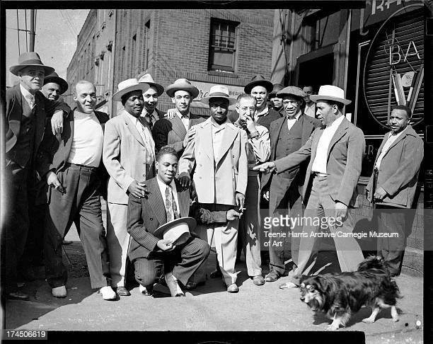 Men standing outside of Crawford Grill No 1 including Bill Snyder third from left Jerry Sumpter in center and William 'Woogie' Harris pointing with...