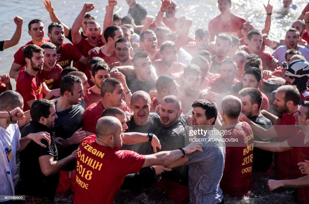 Men struggle as they try to leave the freezing waters of the Vardar River in Skopje on January 19, 2018, during the traditional holiday of Vodici (Epiphany). Macedonians celebrate on this day the Baptism of Christ and Orthodox Christian priests consecrate the waters of lakes and rivers by throwing in a cross and local men race to find it. According to popular belief, the one who finds it will have a year of good luck.