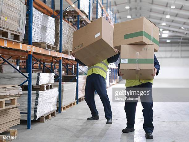 Men Struggling With Boxes In Warehouse