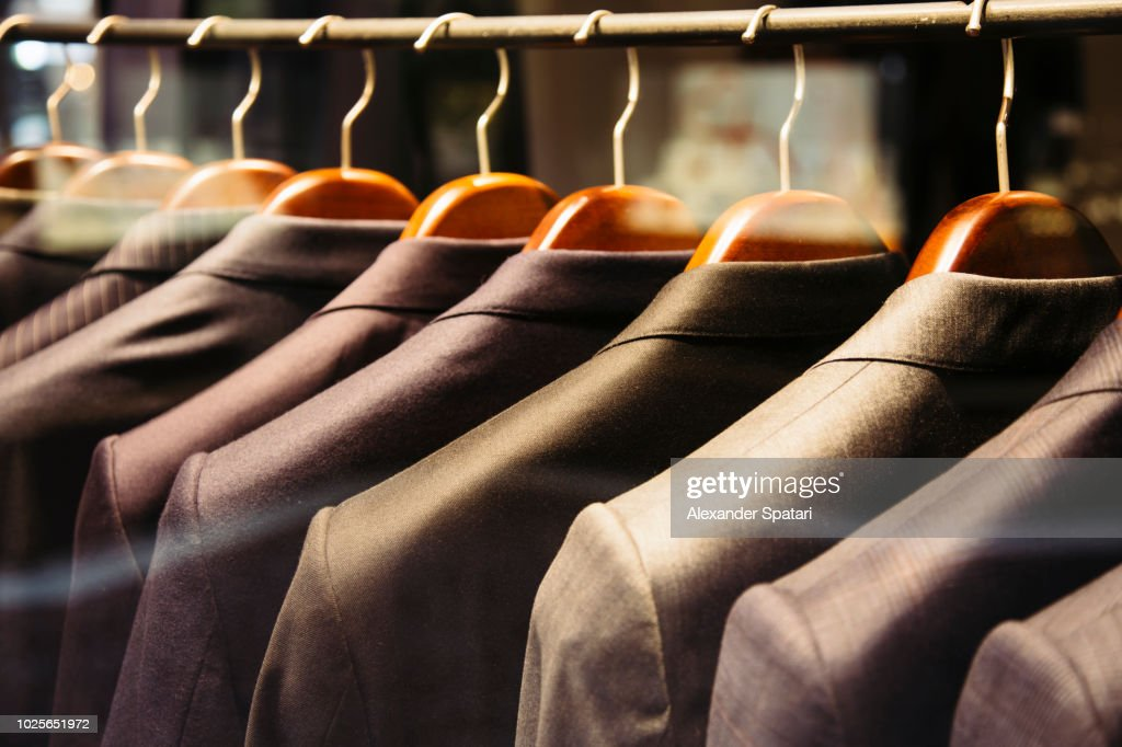 Men suits hanging on a rack, close up : Stock Photo