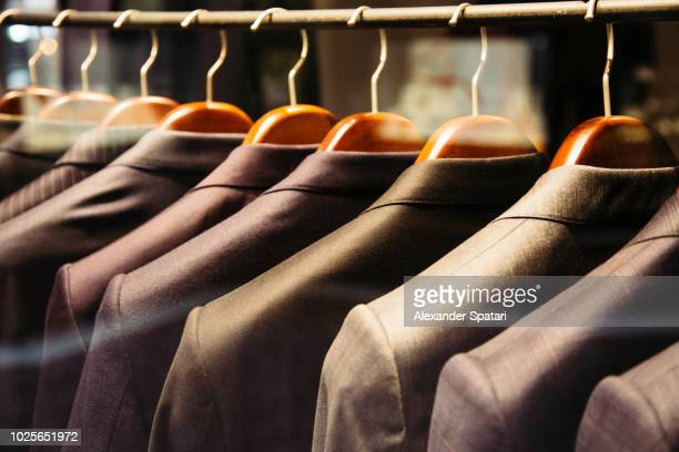men suits hanging on a rack, close up - stereotypically upper class stock pictures, royalty-free photos & images