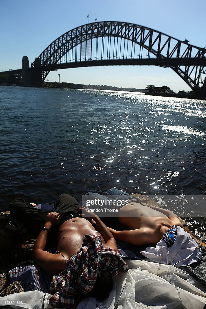 Men sunbake along the harbour prior to New Years Eve celebrations on Sydney Harbour on December 31, 2012 in Sydney, Australia.
