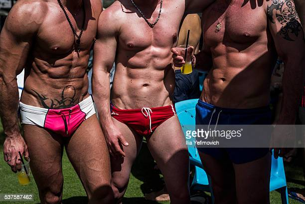 Men sunbathe in swimming trunks as tourists and Israelis enjoy a water park party during a pride week activities on June 2 2016 in Shefayim Israel...