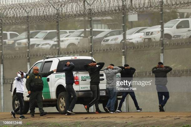 Men surrender to United States Border Patrol agents after jumping a fence in an attempt to get into America on January 17, 2019 in Tijuana, Mexico....