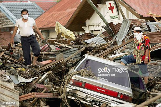Men survey the wreckage of a neighborhood January 3 2005 in Banda Aceh Indonesia The province of Banda Aceh one of the worst hit regions in last...