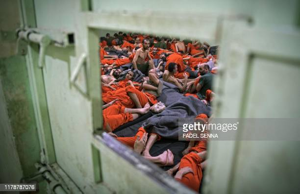 Men, suspected of being affiliated with the Islamic State group, gather in a prison cell in the northeastern Syrian city of Hasakeh on October 26,...