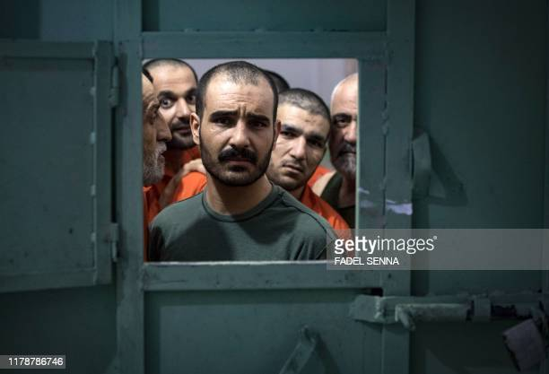 Men, suspected of being affiliated with the Islamic State group, look out of the opening of a prison cell in the northeastern Syrian city of Hasakeh...