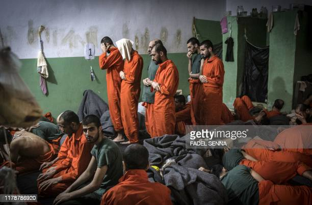 TOPSHOT Men suspected of being affiliated with the Islamic State group pray in a prison cell in the northeastern Syrian city of Hasakeh on October 26...