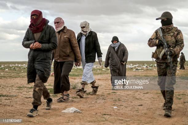 Men suspected of being an Islamic State group's fighter walk next to a member of the Kurdishled Syrian Democratic Forces as they wait to be searched...
