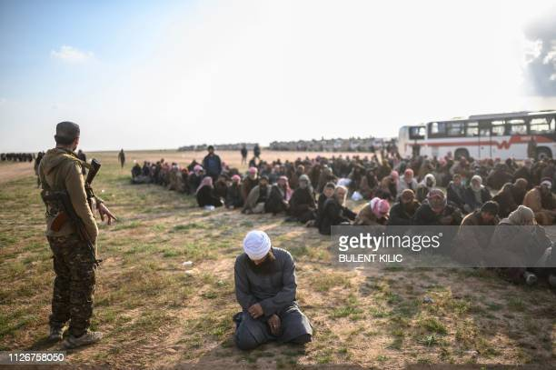Men suspected of being Islamic State fighters wait to be searched by members of the Kurdishled Syrian Democratic Forces after leaving the IS group's...