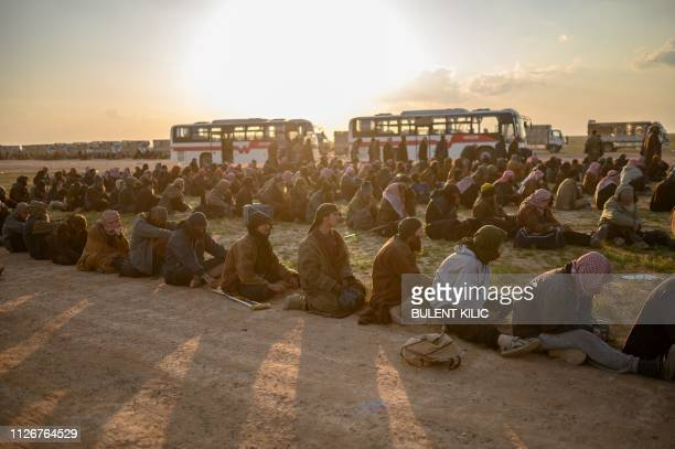 Men suspected of being Islamic State fighters wait to be searched by members of the Kurdish-led Syrian Democratic Forces after leaving the IS group's...