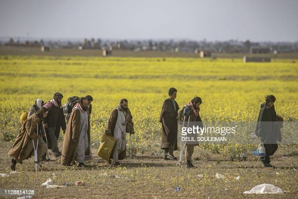Men suspected of being Islamic State group fighters walk together towards a screening point for new arrivals run by US-backed Syrian Democratic...